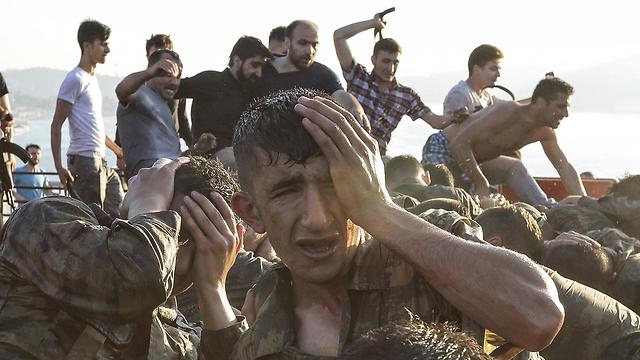 """10:45: כמעט כל כיסי ההתנגדות הוכנעו. בתמונות מטורקיה נראים תומכי ארדואן מכים חיילים שהשתתפו בניסיון ההפיכה ומצליפים בהם בחגורות. הרמטכ""""ל הזמני: כיס ההתנגדות האחרון הוא של חיילי הפיכה המתבצרים במטה הכוחות המזוינים - אבל גם הם ביקשו להיכנע, בכפוף למשא ומתן (צילום: gettyimages) (צילום: gettyimages)"""