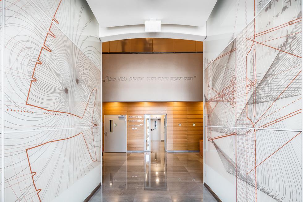 בכניסה למגדל, בדרך למעליות, עוברים בין לוחות מודפסים בעיצובו של ליאו רופמן עם דימויים תעופתיים ופסוק תנ''כי (צילום: אינסה ביננבאום)
