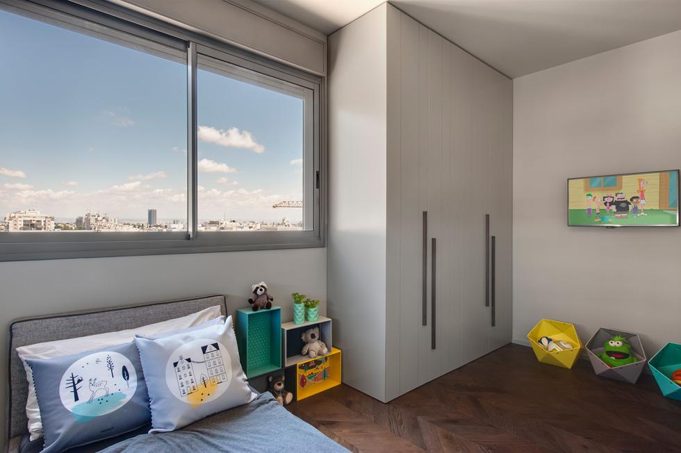 שלושת חדרי הילדים רוצפו ורוהטו מחדש, באותם גוונים אפרפרים ורגועים. תוספות צבע מינוריות הוכנסו באמצעות ארגזי צעצועים, כריות ותמונות (צילום: עודד סמדר)