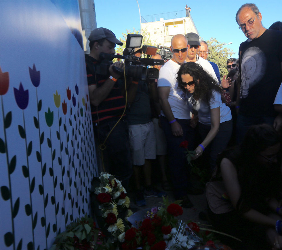Shira Banki's mother, 2016 Pride March, lays a flower at the site where her daughter was stabbed (Photo: Gil Yohanan)