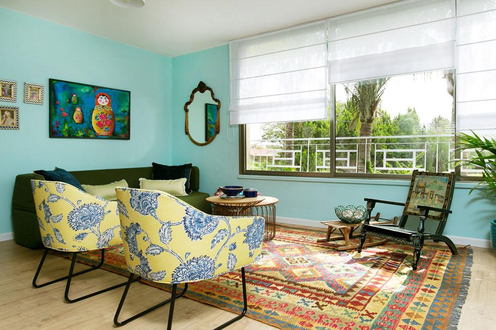 לצד הרהיטים החדשים כורסת עץ נמוכה מהודו ומזחלת עץ ישנה המשמשת כשולחן צד. שטיח גדול מלכד הכל (צילום: שירן כרמל)