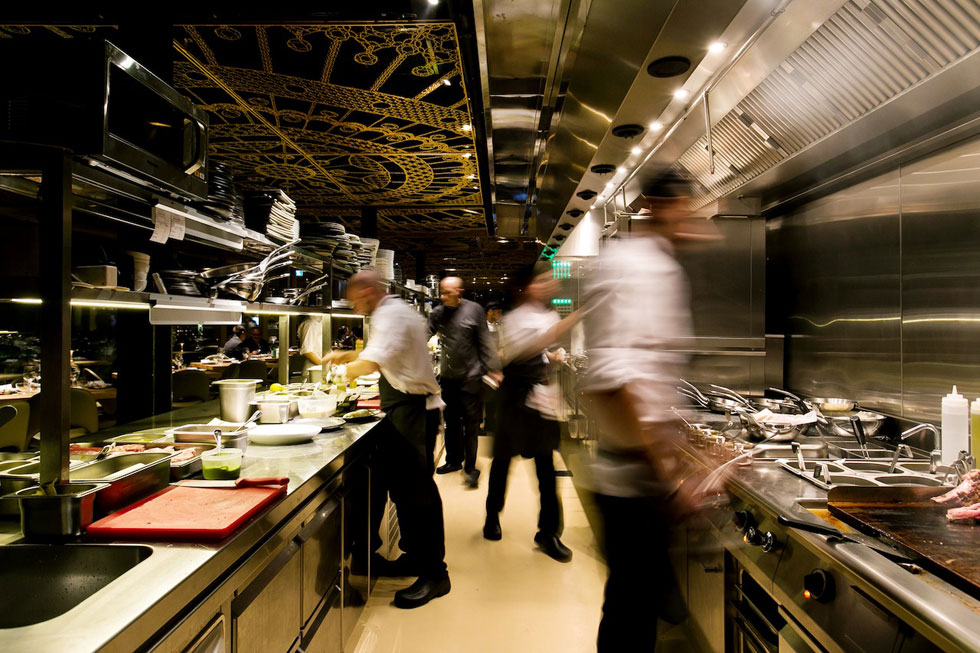 המטבח ממוקם במרכז המסעדה, ופתוח אליה מכל צידיו. כאן החומריות שונה לחלוטין, והיא מעשית ותעשייתית (צילום: שירן כרמל)