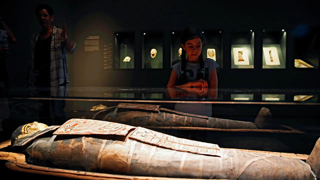 "A girl looks at a 2200-year-old Egyptian mummy, the only mummy in Israel, who according to the museum was a 30-40 year old male named ""Iret-hor-r-u"", meaning the ""Protective Eye of Horus"", on display at the Israel Museum in Jerusalem (Photo: Reuters)"