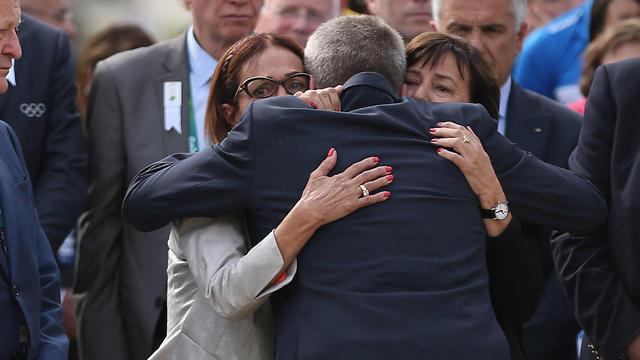 IOC President Thomas Bach, back to camera, embraces Ilana Romano, right, and Ankie Spitzer (Photo: AP)