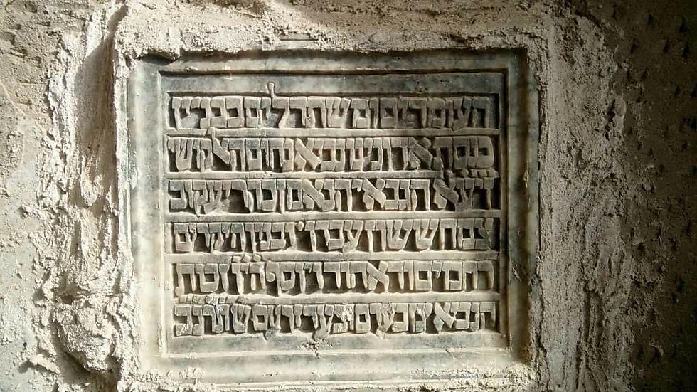 """""""העומדים ומשתדלים בבניין כנסת אדוננו נביא נחום האלקושי זיע""""א"""". כתובת על קיר הקבר (צילום: שרדאר)"""