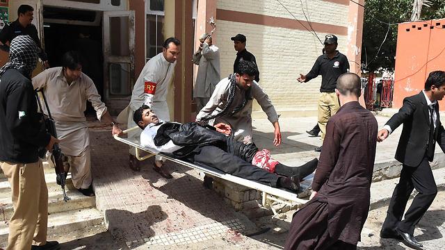פינוי פצוע מזירת הפיגוע בעיר קטה, פקיסטן (צילום: AFP) (צילום: AFP)