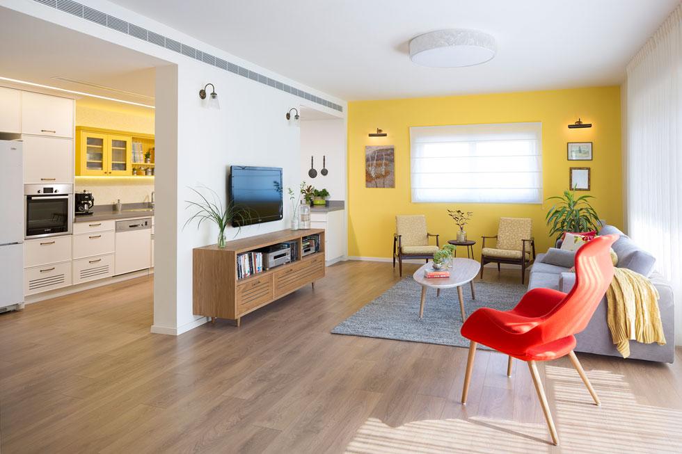 בעלת הבית היא ציירת שאוהבת צבעים. בשל גוני הרהיטים העתיקים בחרה המעצבת להיזהר, והחליטה לצבוע בצהוב רק את הקיר המרכזי בסלון ואת הארונות העליונים במטבח (צילום: שי אפשטיין)