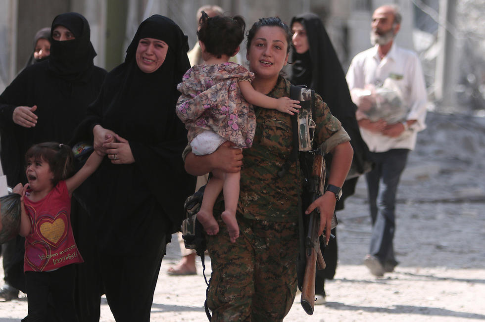 A female Kurdish fighter helps evacuate civilians from Manbij (Photo: Reuters)
