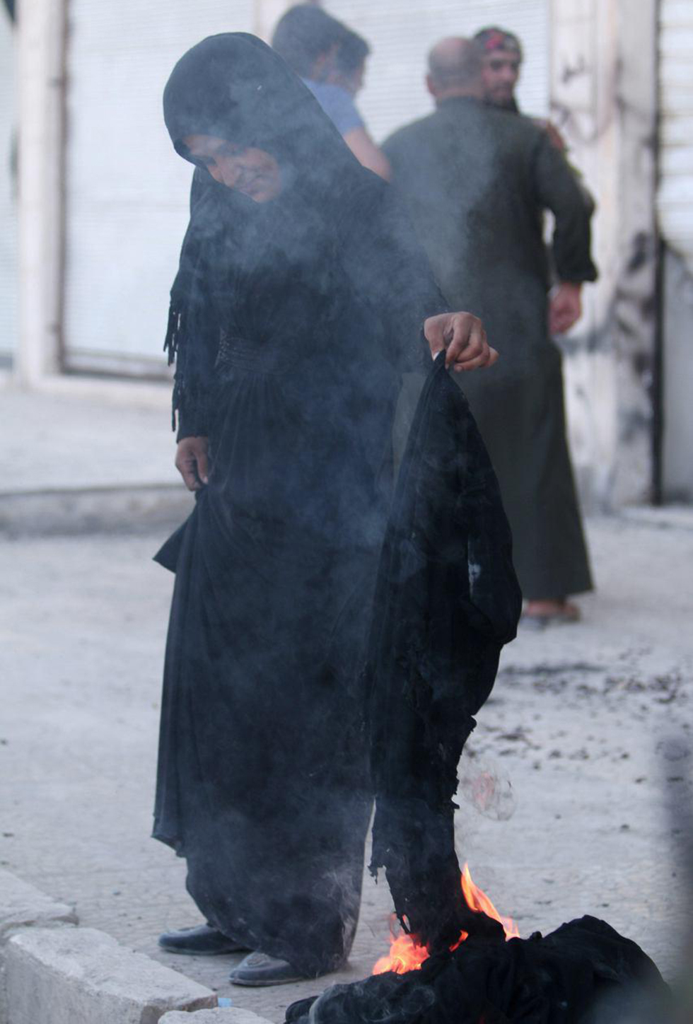 A woman burns her Niqab in Manbij after it's liberation by SDF forces. ISIS imposes a strict Islamic dress code on the population under its control (Photo: Reuters)