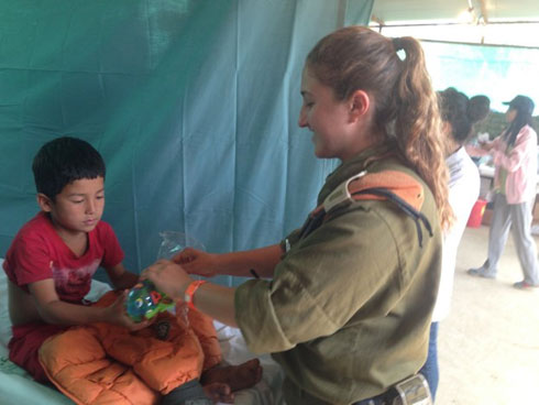 """עם ילד נפאלי. """"קשה ומזעזע, אבל חוויה מדהימה"""" (צילום: דובר צה""""ל)"""