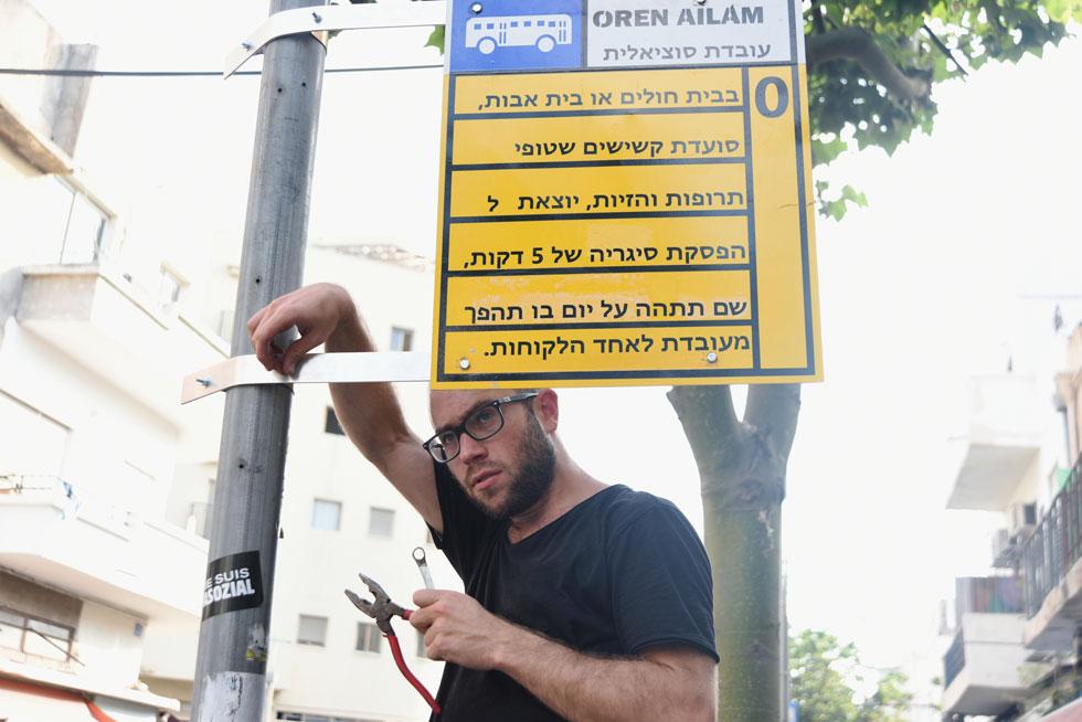 """עילם מתקין שלט עם שירו """"עובדת סוציאלית"""" בתחנת אוטובוס בתל אביב (ראו גם סרטון למעלה) (צילום: שירי קליין נהרי)"""