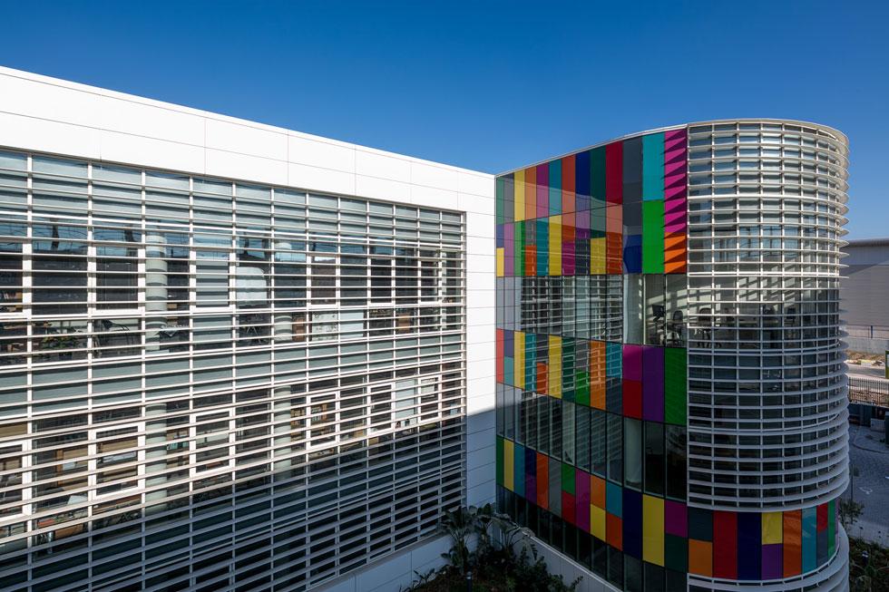 מבנה גלילי מחופה זכוכית (מימין) מאכלס את חדרי הישיבות וחללי העבודה המשותפים. משמאלו נמצא אגף המשרדים, שבו מתבצעת עיקר העבודה של ההוצאה (צילום: עוזי פורת)