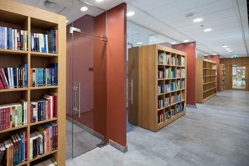 ההפרדה בין חדרי העבודה למסדרון בנויה כספרייה דו-צדדית (צילום: עוזי פורת)