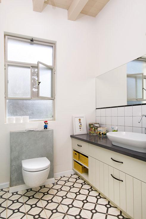 חדר הרחצה שבקומה הראשונה חופה באריחים לבנים.  לרצפה נבחרו אריחים בדוגמה גיאומטרית כהה (צילום: שירן כרמל)
