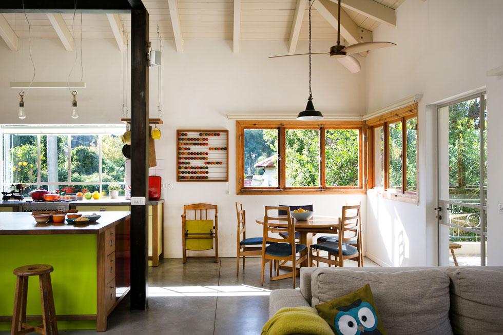 פינת האוכל והמטבח בקומת הקרקע. חלונות העץ  המקוריים, הנפתחים בשיטת אקורדיון, שופצו ושומרו. על הקיר תלויה חשבונייה ישנה של בעלת הבית ותחתיה כסא קולנוע ישן (צילום: שירן כרמל)