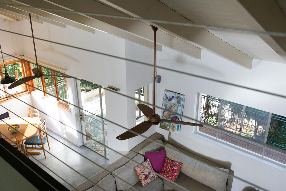מבט מהקומה השנייה אל הסלון, פינת האוכל והיציאה למרפסת. מאווררים גדולים תלויים מהתקרה המשופעת. החלל הגבוה והפתוח יוצר קשר בין הקומות (צילום: שירן כרמל)