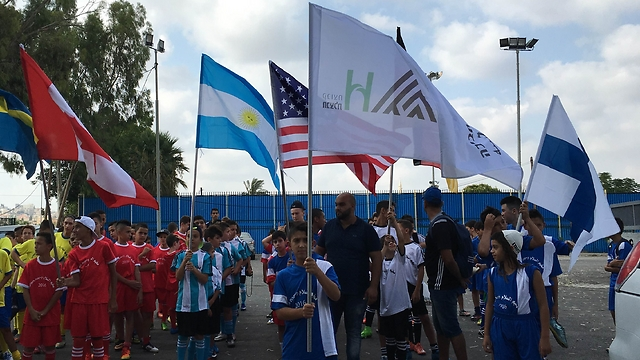 "Campers raising the flags of the countries ""competitng"" in the tournament"
