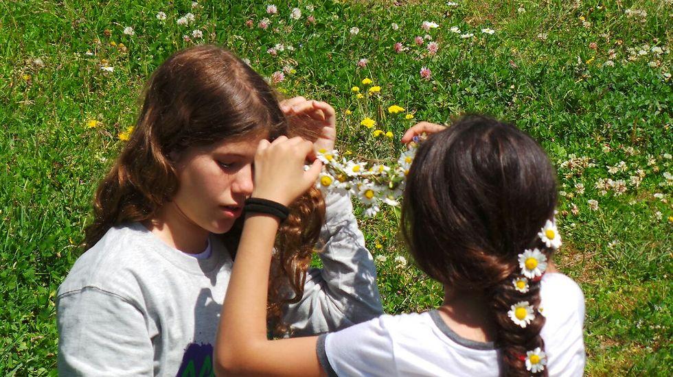 הילדים שהפכו לחברים כאילו שהם מכירים כבר מהגן. ענהאל ועדן שוזרות אחת לשניה פרחים בשיער. (צילום: משה גלנץ)