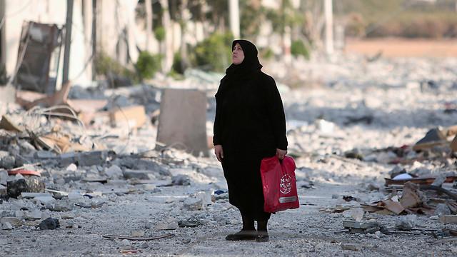 זירת הקרב המשמעותית ביותר בסוריה. אישה ברחוב הרוס בחלב (צילום: רויטרס) (צילום: רויטרס)