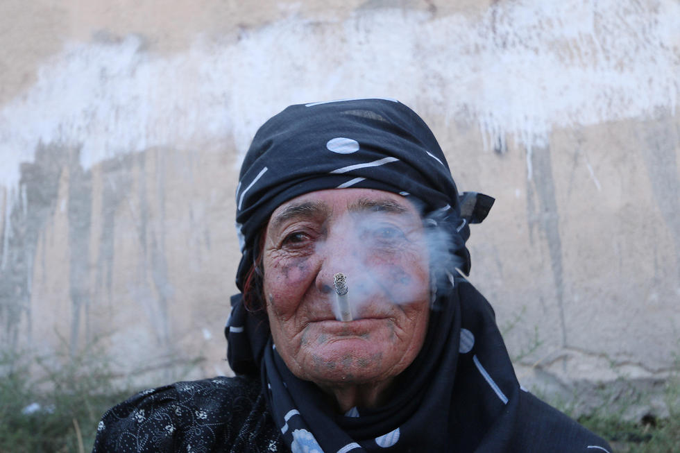 A Manbij woman smoking after the city's release (Photo: Reuters)