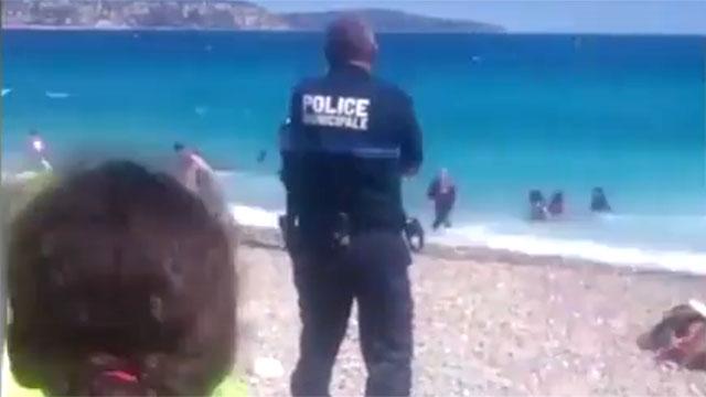 שוטר מחכה שנשים בלבוש איסלאמי ייצאו מהמים בניס ()