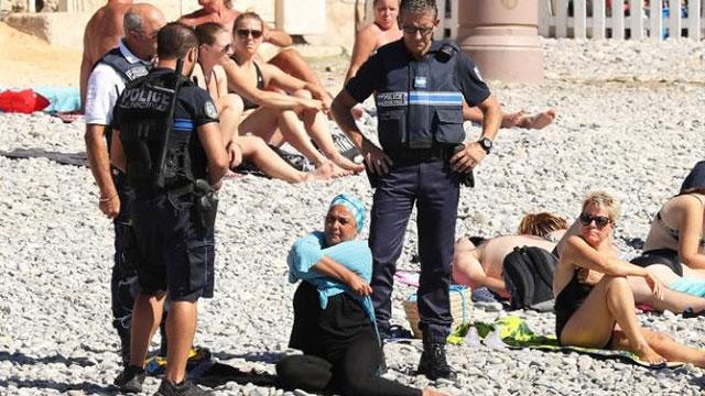 שוטרים ומוסלמית עם בורקיני בחוף של ניס (צילום: Vantagenews)