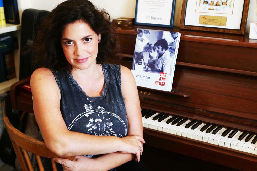 """קרן רוזנבלום-פולק בביתה בתל אביב, ליד הפסנתר של אביה. """"יש כאן איזושהי הכרה שהוא לא זכה לה בחייו"""" (צילום: צביקה טישלר)"""