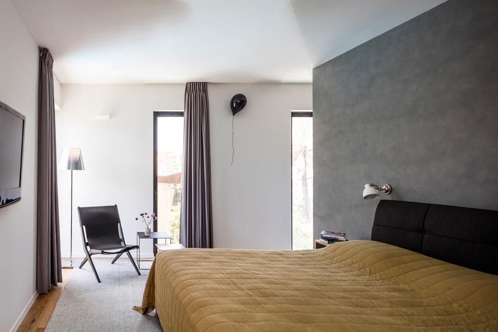 חדר ההורים נהנה משלושה כיווני אור ואוויר. מאחורי הקיר האפור שבגב המיטה תוכנן איזור ארונות ורחצה (צילום: עמית גרון)