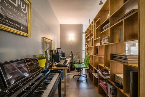 """""""אני עובד הרבה בבית, בעיקר בלילות, והיה חשוב לי ליצור בחלל המרכזי חלוקה בין הסלון לבין האולפן שלי, באמצעות מחיצה של ספריית כוורת"""" (צילום: איתי סיקולסקי)"""
