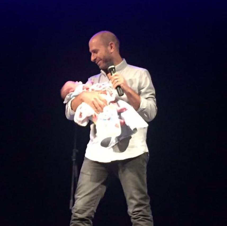 עם התינוק שבכה בקהל ונרגע בזרועותיו
