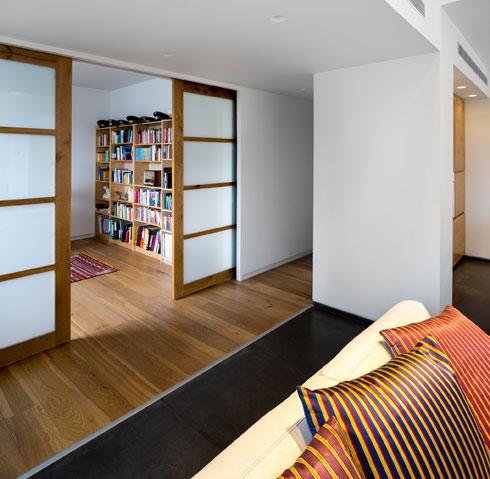 חדר העבודה מופרד מהסלון בדלתות הזזה מעץ וזכוכית חלבית (צילום: איתי אבירן)