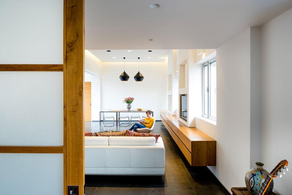 חדר עבודה מרווח מוסתר מאחורי דלתות הזזה גדולות מעץ אלון וזכוכית חלבית, המשמשות, כשהן סגורות, כמעין קיר תוחם של הסלון (צילום: איתי אבירן)