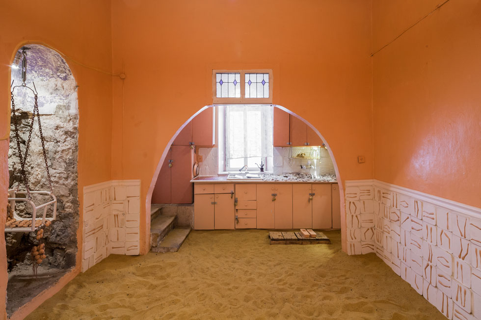 הרצפה בחדר הזה כוסתה בשכבה עמוקה של חול, ואת הקירות מכסים אריחים שבהם שולבו חלקי בובות. המטבח הוורוד בקצה נראה מאיים (צילום: טל ניסים)
