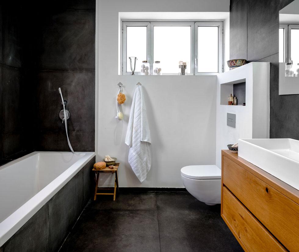אריחי בזלת שחורה מכסים גם את קירות חדר הרחצה, כמו את רצפת הסלון (צילום: איתי אבירן)
