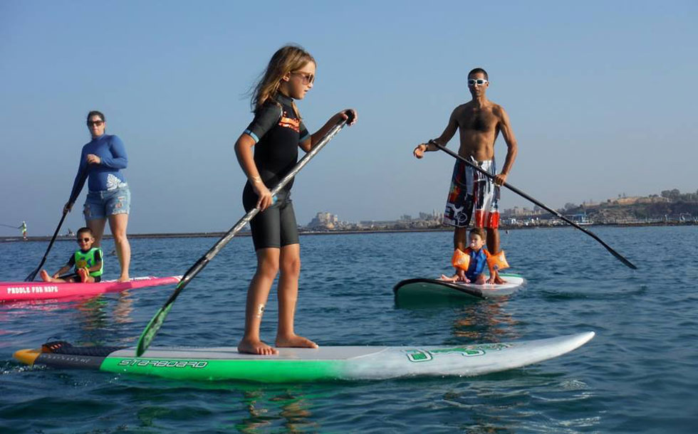 """עם אשתו וילדיו בים. """"הילדים שלי חיים את המים ואת הספורט מגיל אפס: הם רצים, שוחים, צוללים, גולשים על סאפ, לפעמים גם על גלשן רוח"""" (צילום: אלבום פרטי)"""