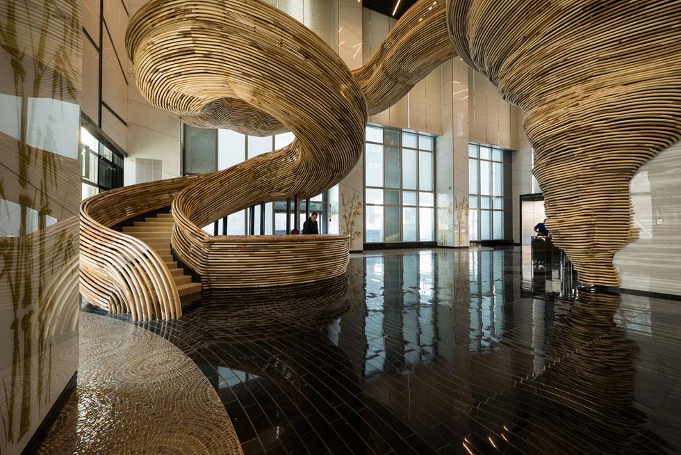 הלובי של מגדל המשרדים ''אמות אטריום'' ברמת גן, בתכנון עודד חלף. טורנדו ענק, עשוי מוטות עץ עגולים מכופפים, מסתיר גרם מדרגות (צילום: איתי סיקולסקי)
