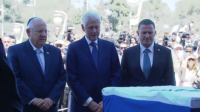 Former US President Bill Clinton stands with President Reuven Rivlin (l) and Yuli Edelstein (r) as he bids his final farewell to Shimon Peres
