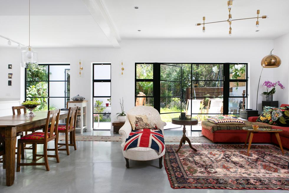את הסלון הפנו למזרח ולגינה האחורית, וקורת פלדה לבנה מחליפה קיר. הרצפה עשויה בטון, פרופילי החלונות צבועים בפחם, הספה האדומה מניו דלהי ומולה שזלונג משוק פורטובלו בלונדון (צילום: שירן כרמל)