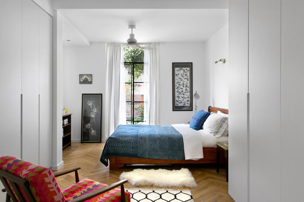 חדר ההורים. האהבה לטקסטיל מתבטאת כאן, בין היתר, בכיסוי המיטה ההודי וברשתות הדפס של בדי קימונו, שמוסגרו ומעטרות את הקירות (צילום: שירן כרמל)