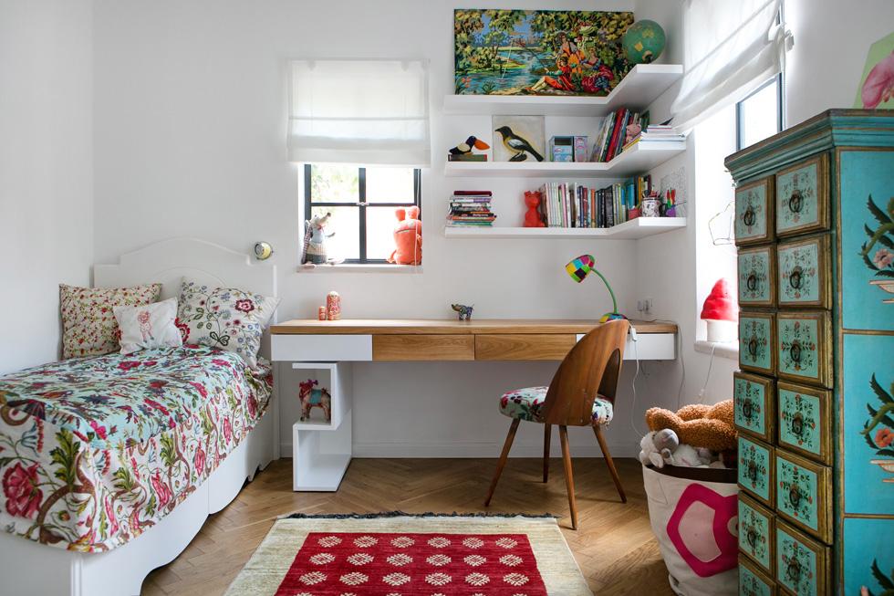 חדרה של אליה בת העשר. כיסוי המיטה ושידת הטורקיז מהודו, השולחן הוזמן מנגר, השטיח מאיסטנבול, מנורת השולחן הצבעונית מלונדון (צילום: שירן כרמל)