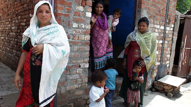 Neighbors of Jehangir, a Christian who had converted to Islam for his beloved Tasleem, stand outside their home in Lahore (Photo: AP)