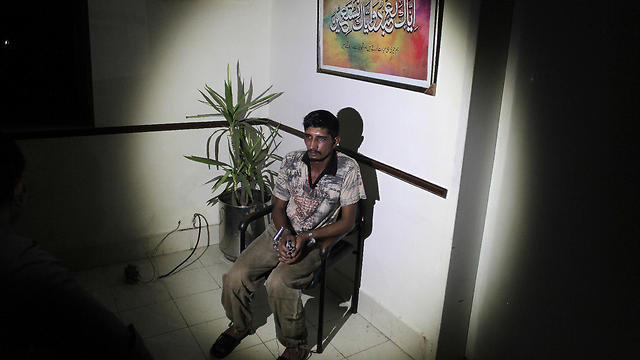 Mubeen Rajhu, who killed his sister Tasneem sits at police headquarters in Lahore (Photo: AP)