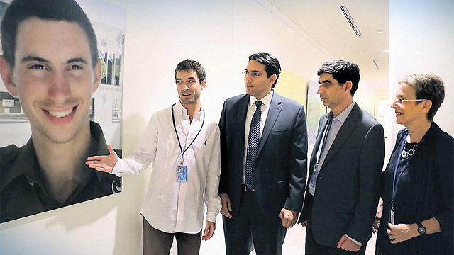 From the right: Leah and Simcha Goldin, Israeli Ambassador to the UN Danny Danon and Hadar Goldin's twin brother, Tzur, with a picture of Hadar at the UN (Photo: Kobi Gideon, GPO) (Photo: Kobi Gidon)