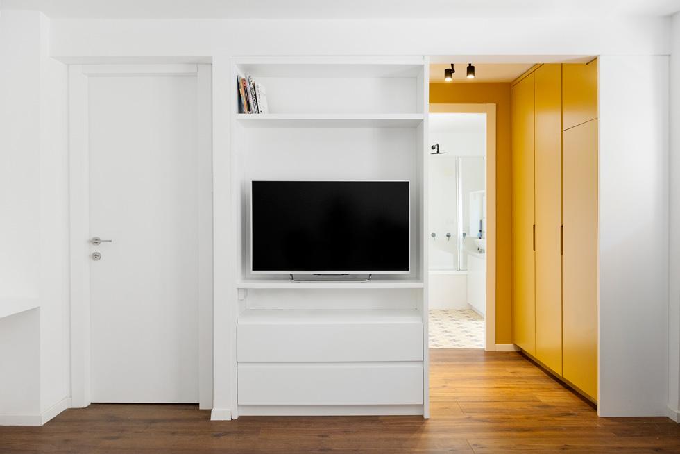 חדר ארונות פתוח, צהוב כולו, מקשר בין חדר השינה לחדר הרחצה. הצהוב חוזר באריחי הבטון המצוירים (צילום: גדעון לוין)