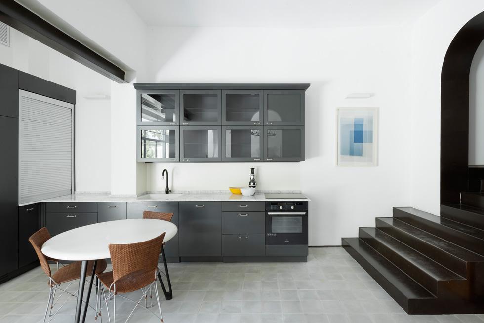 במטבח השחור השתלט על הלבן וגם המדרגות שמובילות לחצאי הקומות שבהם חדרי האירוח, למעלה ולמטה, עשויות ברזל שחור (צילום: גדעון לוין)