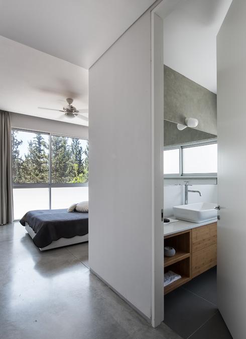 לחדר השינה קיר זכוכית ויציאה ישירה למרפסת האחורית. וילונות כהים שמוסיפים אינטימיות ומאפשרים החשכה מלאה (צילום: עמית גושר)