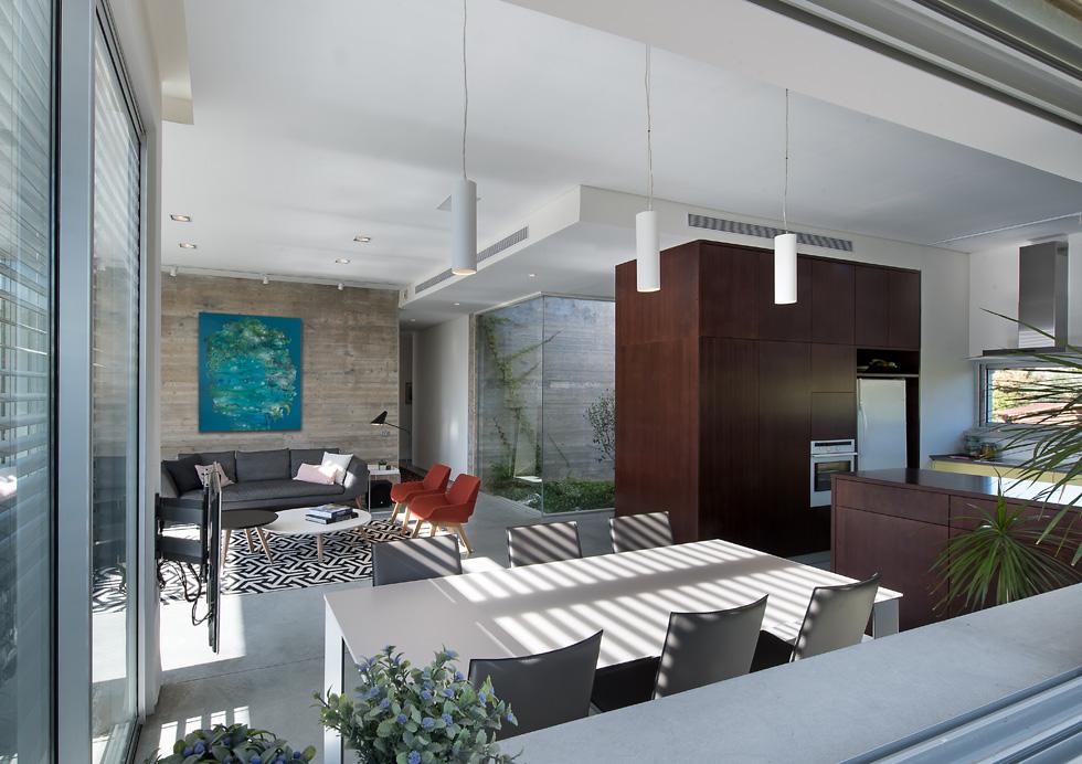 ארונות המטבח הצהובים, הכורסאות האדומות והציור על הקיר מקלילים את הצבעוניות הטבעית של הבית. אם יוחלט בעתיד להוסיף קומה, הפטיו יהפוך לגרם מדרגות (צילום: עמית גושר)
