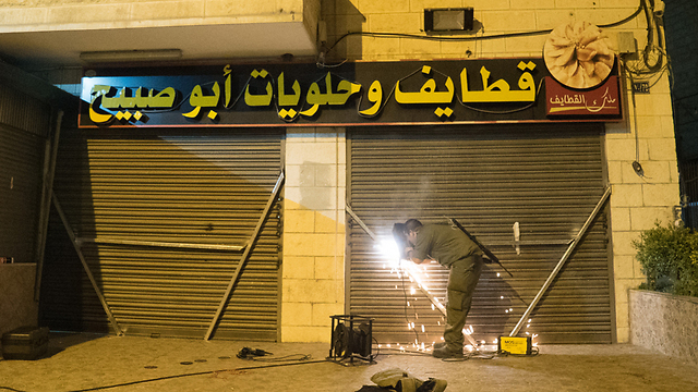 An IDF soldier working on welding shut the entance to the terrorist's family's sweet shop (Photo: IDF Spokesperson's Unit)