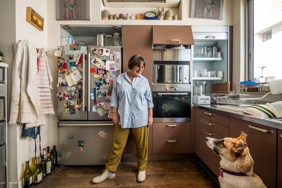 """""""בישול זו פעולה שמאוד מרגיעה אותי. אם אני בסטרס, אני נכנסת לבשל"""". סיביל גולדפיינר במטבח ביתה עם הכלב בוסה (צילום: איתי סיקולסקי)"""