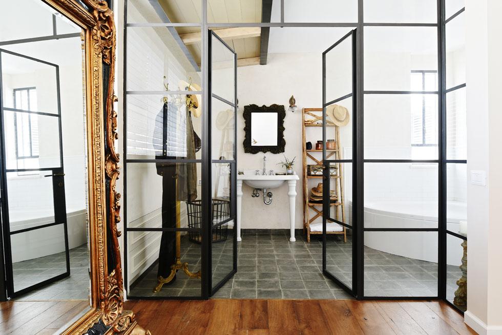 חדר ההורים והאמבט הצמוד אליו מופרדים זה מזה על ידי דלת זכוכית מחולקת בדוגמת ריבועים  (צילום: שי אדם)